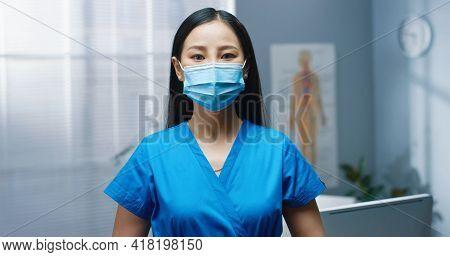 Asian Young Beautiful Female Professional Nurse Wearing Medical Mask And Uniform Standing In Hospita