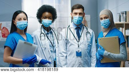 Portrait Of Happy Young Mixed-race Doctors And Nurses In Medical Masks Standing In Medical Center Lo