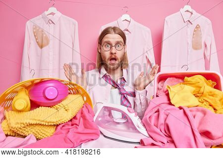 Overwhelmed Bearded Redhead Man Embarrassed As Has Much Work To Do Irons Laundry At Home Stands Near