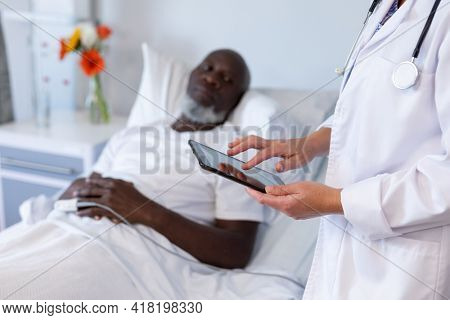 Caucasian female doctor standing next to african american male in hospital patient room using tablet. medicine, health and healthcare services.