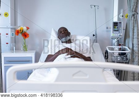 Portrait of african american male patient lying on hospital bed looking to camera. medicine, health and healthcare services.
