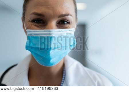 Portrait of happy caucasian female doctor wearing mask standing in hospital corridor. medicine, health and healthcare services during coronavirus covid 19 pandemic.