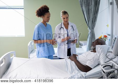 Two diverse female doctors and african american male patient in hospital room talking. medicine, health and healthcare services.
