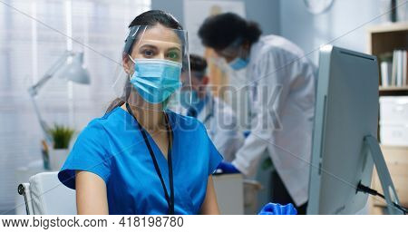 Close Up Portrait Of Happy Caucasian Pretty Young Female Nurse In Mask And Face Shield Working In Ho