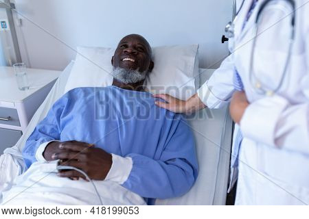 African american male patient lying on hospital bed smiling to female doctor. medicine, health and healthcare services.