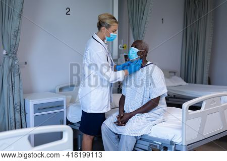 Caucasian female doctor wearing face mask palpating lymph nodes of african american male patient. medicine, health and healthcare services during coronavirus covid 19 pandemic.