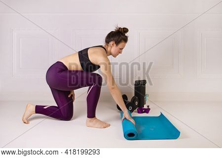 Attractive Young Woman Folding Blue Yoga Or Fitness Mat For Working Out. Strength And Motivation, Sp