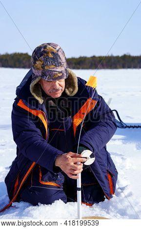 Ice Fishing. Fisherman Fishing On Frozen Lake. Winter Frosty Morning Fishing On River. Vertical Phot