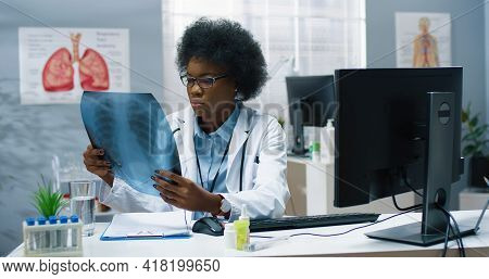 Portrait Of Concentrated Experienced Female Doctor In Medical Coat Sitting At Desk In Hospital Cabin