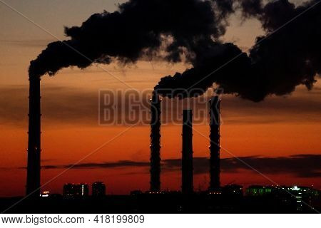 Smoke From Industrial Chimneys At Sunset. Toxic Smoke From A Thermal Power Plant In An Industrial Ar