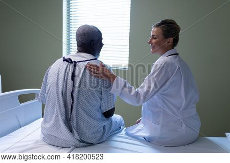 Diverse female doctor and male patient sitting on hospital bed smiling to each other. medicine, health and healthcare services.