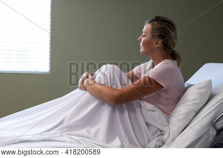 Portrait of caucasian female patient sitting on hospital bed looking ahead. medicine, health and healthcare services.