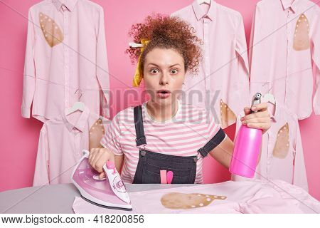 Responsible Curly Haired Woman Maid Stares Bugged Eyes Busy With Housework Stands Near Ironing Desk