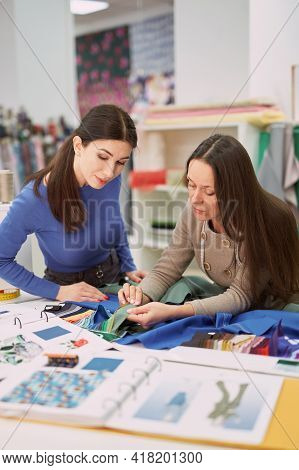 Textile Store, Tailor, Atelier Or Dressmaker Concept. Fabrics Shop Woman Consultant Showing Green Co