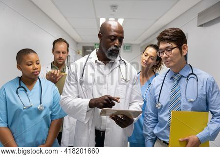 Diverse group of male and female doctors walking through corridor looking at tablet. medicine, health and healthcare services.
