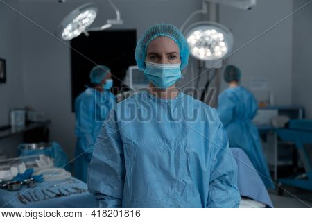 Portrait of caucasian female surgeon wearing face mask, surgical cap and gown in operating theatre. medicine, health and healthcare services during covid 19 coronavirus pandemic.