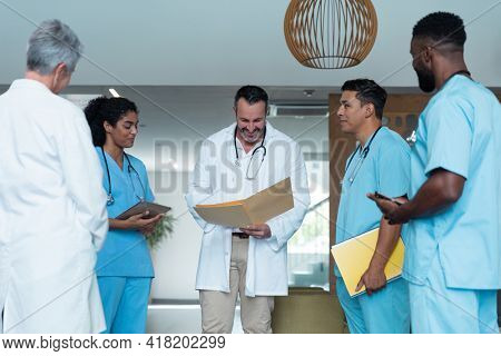 Diverse male and female doctors standing in hospital corridor and discussing. medicine, health and healthcare services.