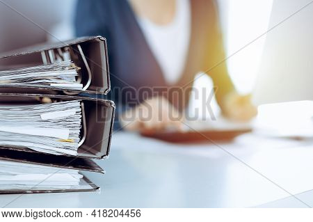 Binders With Papers Are Waiting To Be Processed By Business Woman Or Bookkeeper Working At The Desk