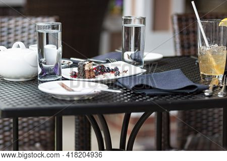 Leftover Food Waste Concept Image Featuring An Outdoor Cafe Table With No Customer But Leftover Cake