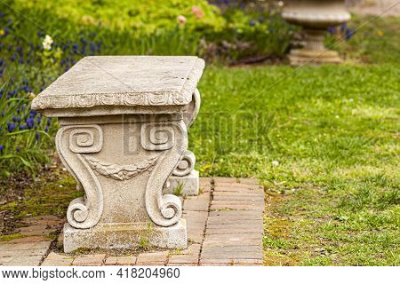 A Vintage Carved Stone Garden Bench On Grass Field In A Park Or Garden. It Has Spiralling Symmetrica