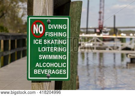 An Extensive List Of Actions Forbidden On The Dock Area Are Shown. The Sign Says No To Diving, Swimm