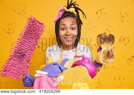 Horizontal Shot Of Happy Housekeeper Smiles Pleasantly Being In Good Mood After Finishing Cleaning A