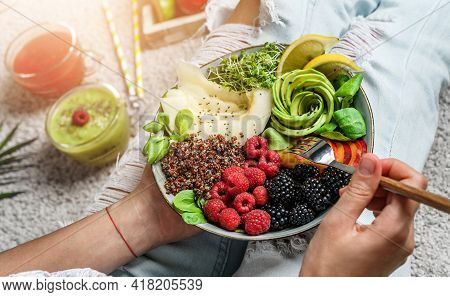 Woman In Jeans Holding Fresh Healthy Green Salad With Quinoa, Peach, Greens, Avocado, Berries, Melon