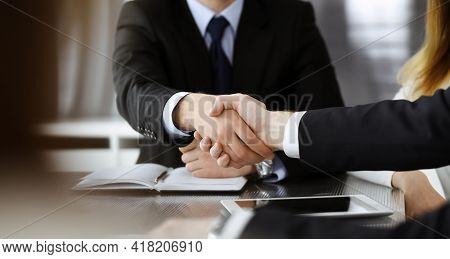 Unknown Businessmen Shaking Hands Above The Glass Desk In A Modern Office, Close-up. Unknown Busines