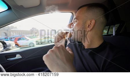 Side Portrait Of Handsome Cruel Serious Young Man Sitting In Car. A Brutal Man With A Beard In A Car