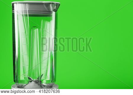 A White Blender With An Empty Glass On A Green Background.