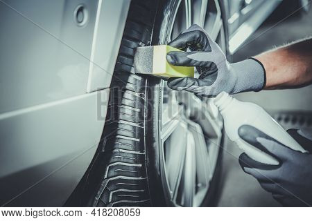 Caucasian Car Detailing Worker Taking Care Of Modern Vehicle Tires And Alloy Wheels. Vehicle Detail