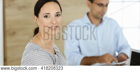 Businesswoman And Businessman Discussing Questions While Using A Computer In Modern Office. Portrait