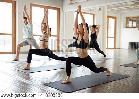 People Stretching At Yoga Class In Fitness Studio. Young Sporty People Practicing Yoga In Modern Spo