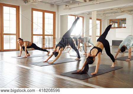 Group Of Young Sporty People Practicing Yoga Lesson With Instructor. Yoga Classes. Fitness, Training