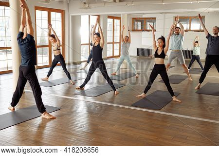 Group Of Young Sporty Attractive People Practicing Yoga Lesson With Instructor. Work Out Physical Ac