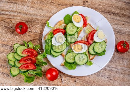 Fried White Bread Toasts With Vegetable And Egg Slices And Cucumber And Tomato Salad On A Plate On A