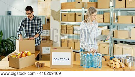 Young Caucasian Male Volunteer Putting Food In A Donation Box As Charity Worker And Member Of The Co