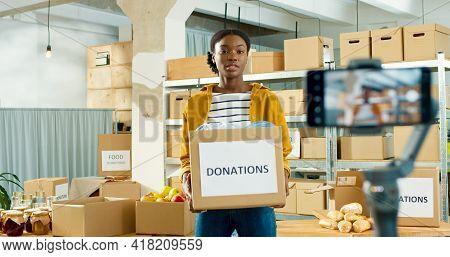 Joyful Young Beautiful African American Woman Volunteer Standing In Warehouse Holding In Hands Donat
