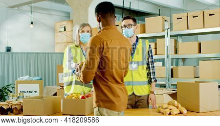 Team Of Caucasian Young Male And Senior Female Charity Workers Giving Food To Poor African American