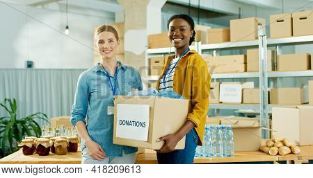 Cheerful Young Beautiful Female Social Workers Preparing Donations Holding Box Parcel In Hands Stand