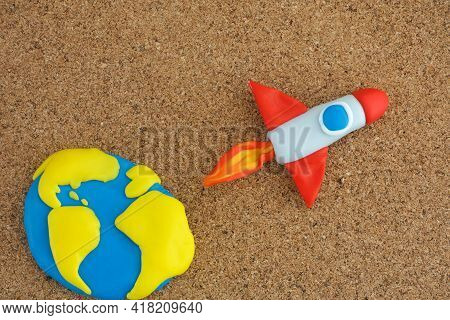Space Rocket Blasting Off For New Ideas. The Earth And The Space Rocket Are Made Out Of Polymer Clay