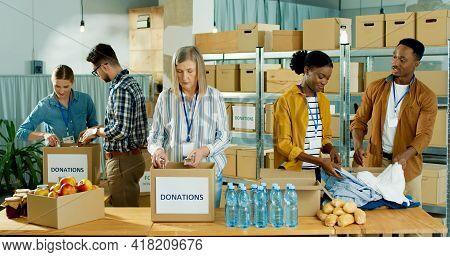 Caucasian And African American People Men And Women Volunteers Working At Charity Organization Packi