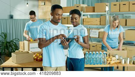 Joyful Young African American Man And Woman Social Workers Work In Charity Organization Texting And