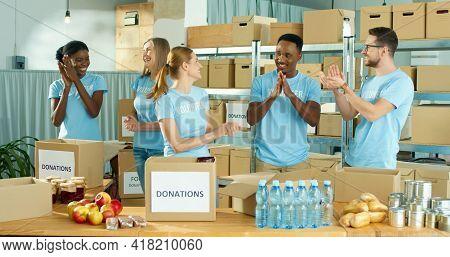 Joyful Happy Diverse Caucasian And African American Men And Women Volunteers Standing In Social Orga
