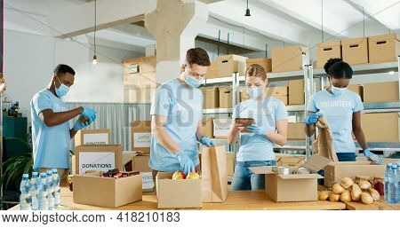 Group Of Mixed-race Young Male And Female Volunteers Putting Food In Packet Sorting Clothes Preparin