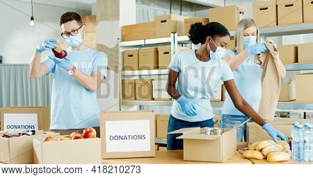Multi-ethnic Busy Charity Organization Workers Man And Women Work In Warehouse Packing Box Parcel Wi