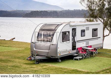 Rv Caravan Camping At The Caravan Park On A Peaceful Lake With Mountains On The Horizon. Camping Vac