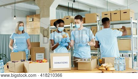 Diverse Mixed-race People Men And Women Working In Warehouse In Charity Organization Collecting And
