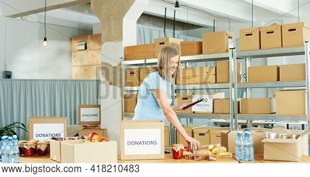 Portrait Of Busy Caucasian Mature Pretty Woman Volunteer Working In Charity Center Warehouse Packing
