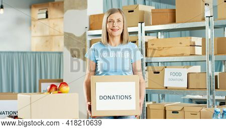 Portrait Of Beautiful Caucasian Happy Mature Woman Social Worker Working In Warehouse Holding In Han